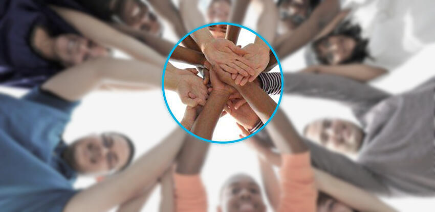 image of a circle of persons with hands together in the center